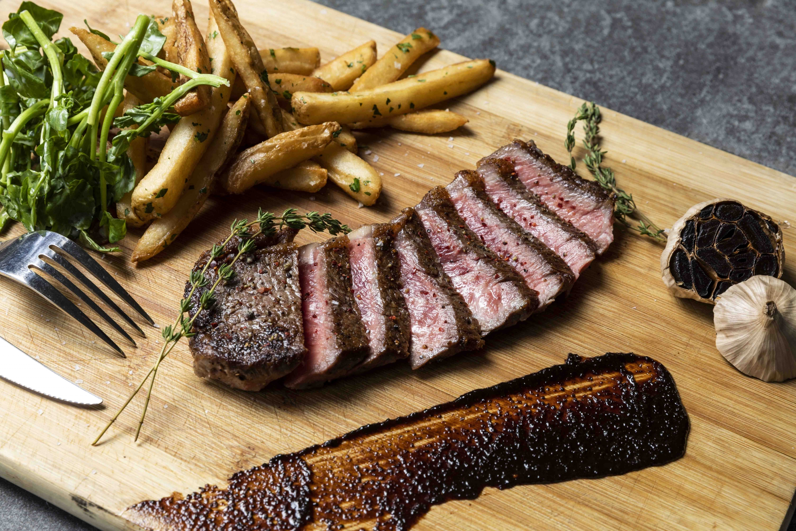 A cut of steak, fries and garlic on a wooden cutting board.