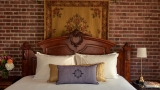 The headboard and brick wall of the Kingscote suite bedroom.