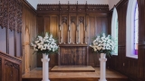 Image of a two flower bouquets in a church.