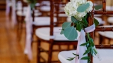 Image of wedding guest seating with a bouquet of flowers.
